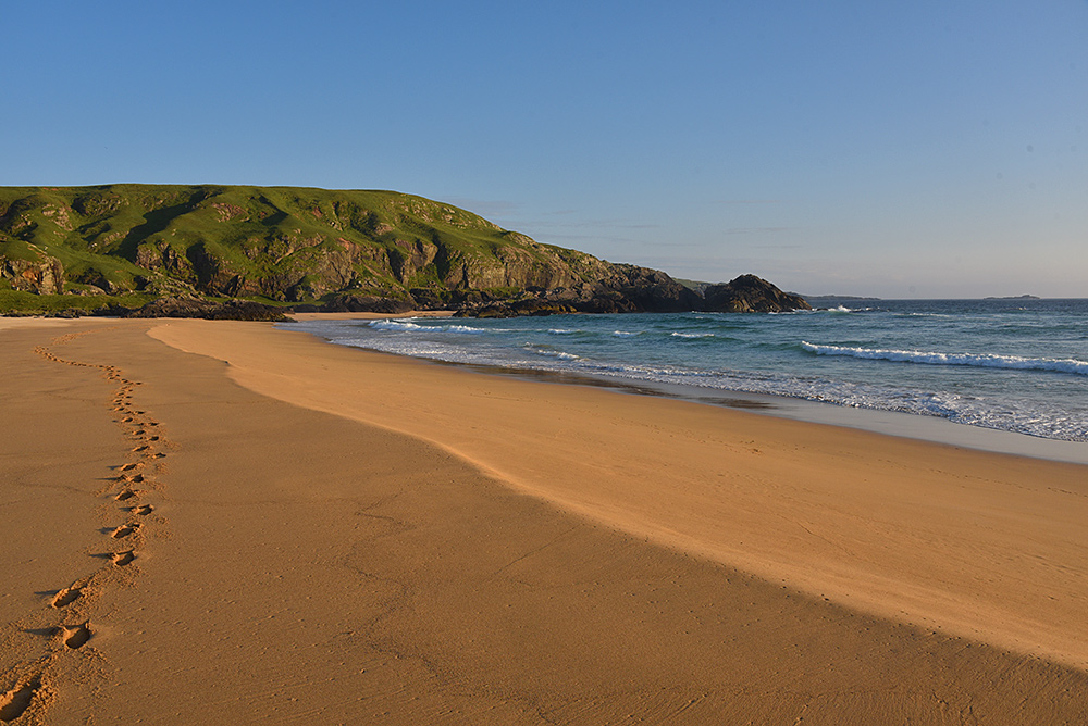 Picture of a beach in a bay in some mild June evening light
