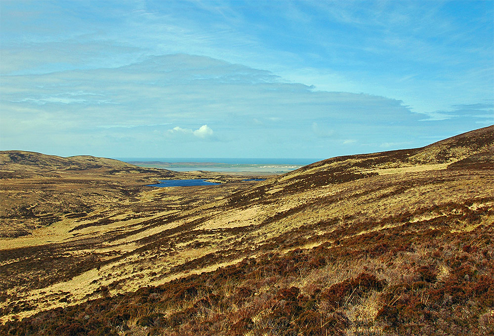 Picture of a remote island landscape, looking towards a distant coast from low hills over a moorland landscape