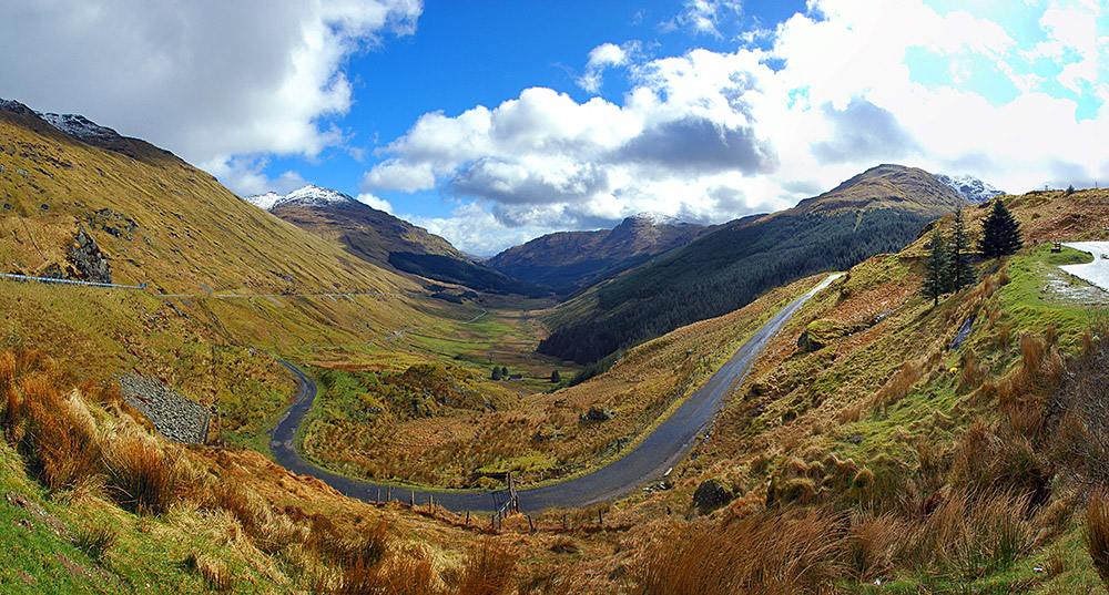 Panoramic picture of a valley with roads snaking up on the side