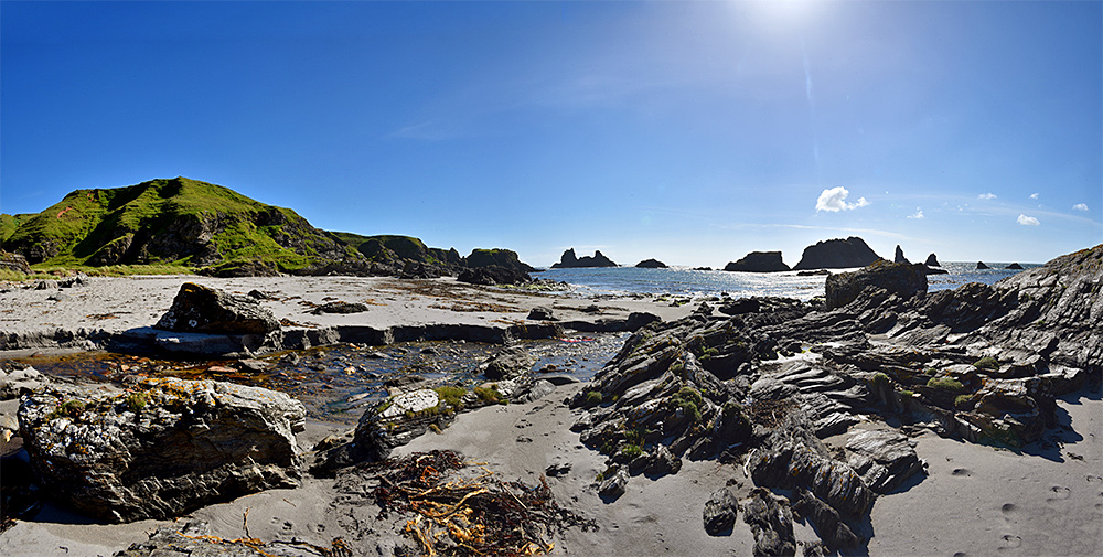 Panoramic picture of a burn (stream) flowing over a beach into the sea
