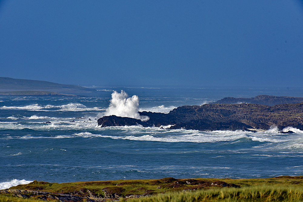 Picture of some big swell rolling towards a rocky shore, waves breaking over the rocks