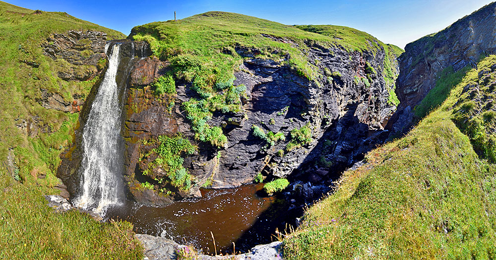 Panoramic picture of a waterfall and its outflow hidden behind an earth wall