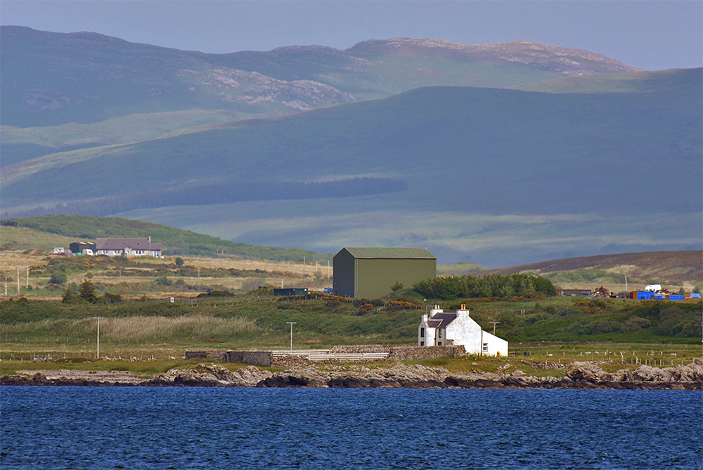 Picture of an old farmhouse on the shore seen across a sea loch, a modern storage building in the background