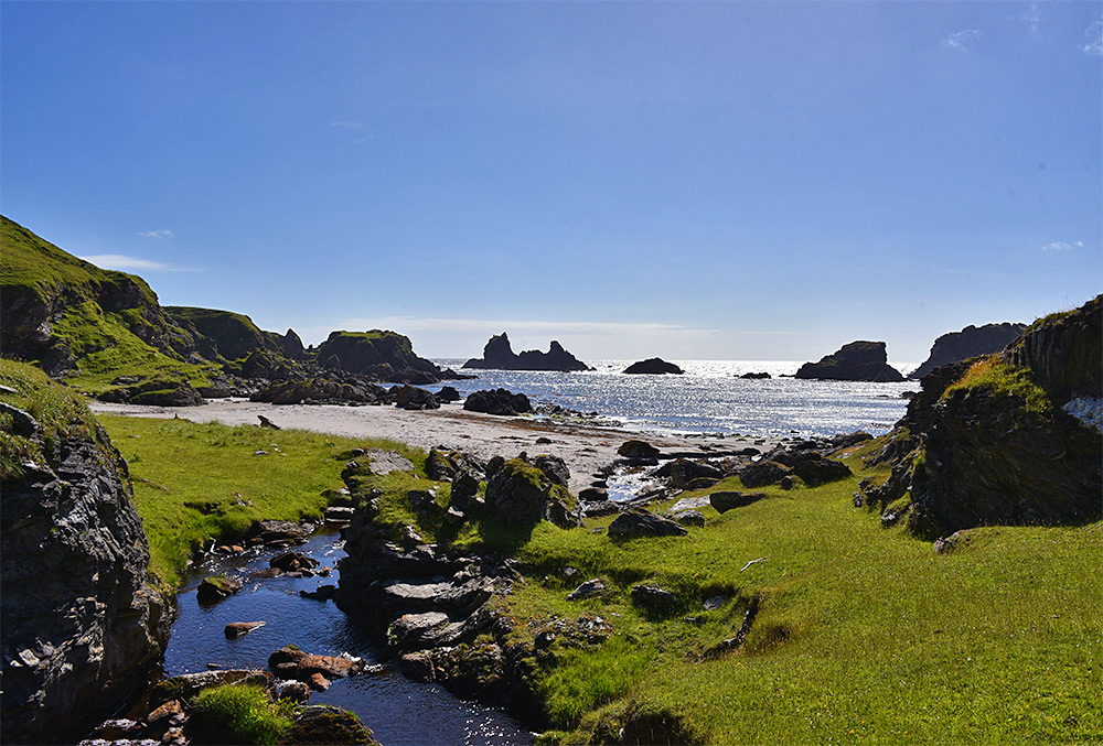 Picture of a sunny June afternoon at a coast with a beach and rock formations