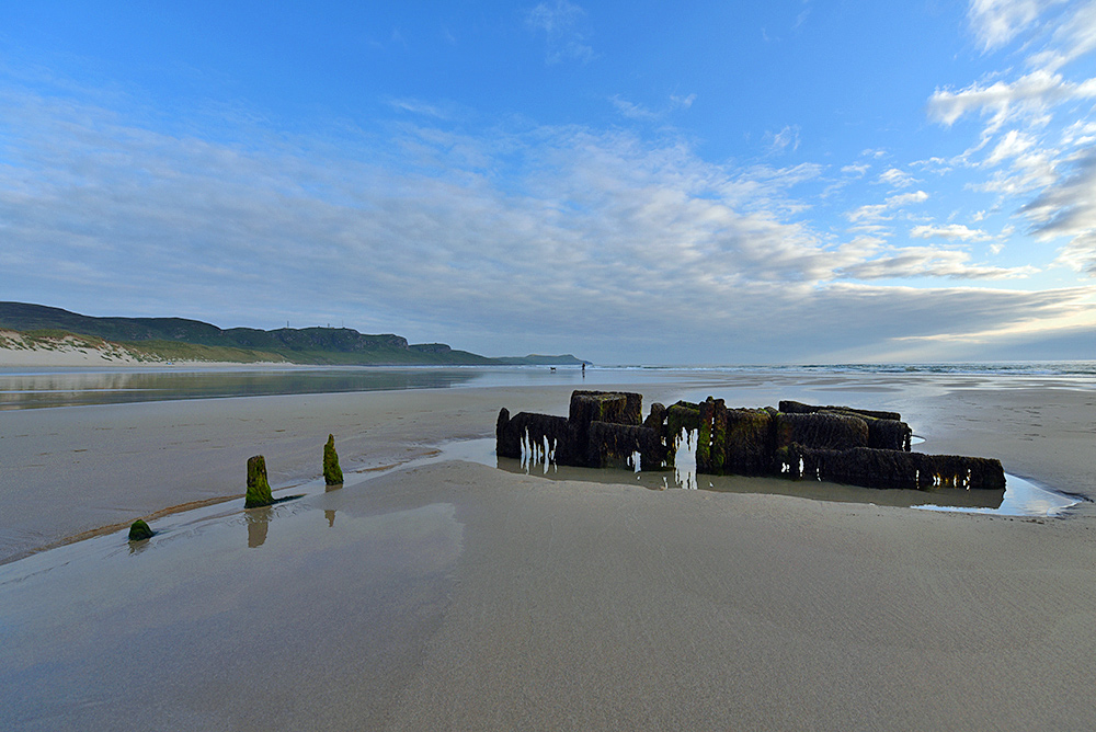 Wide angle lens picture of a wreck on a beach on a calm June evening