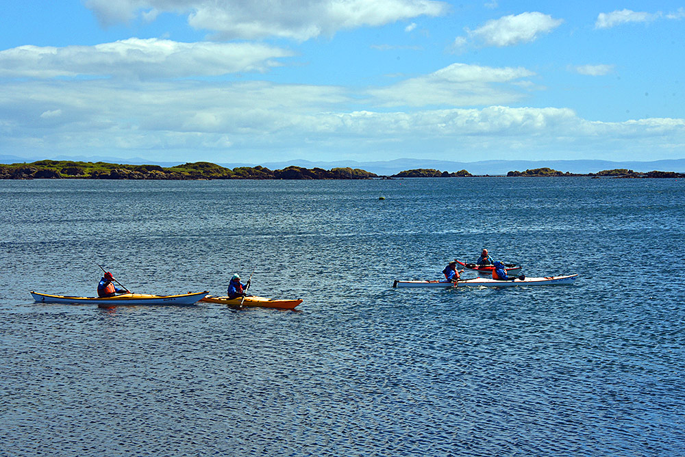 Picture of a group of 4 kayakers with some skerries in the background