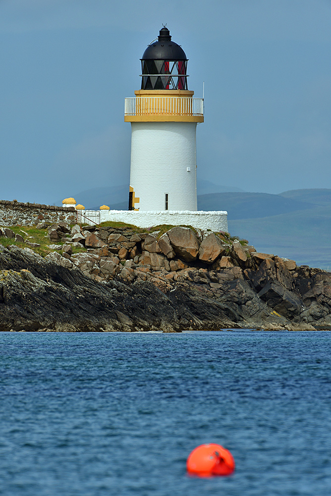 Picture of a small lighthouse with a buoy in the water below it