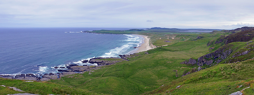 Panoramic picture of a view over a bay with a sandy beach and some crags behind it