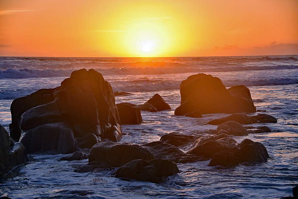 Picture of a sunset behind some rocks on a beach