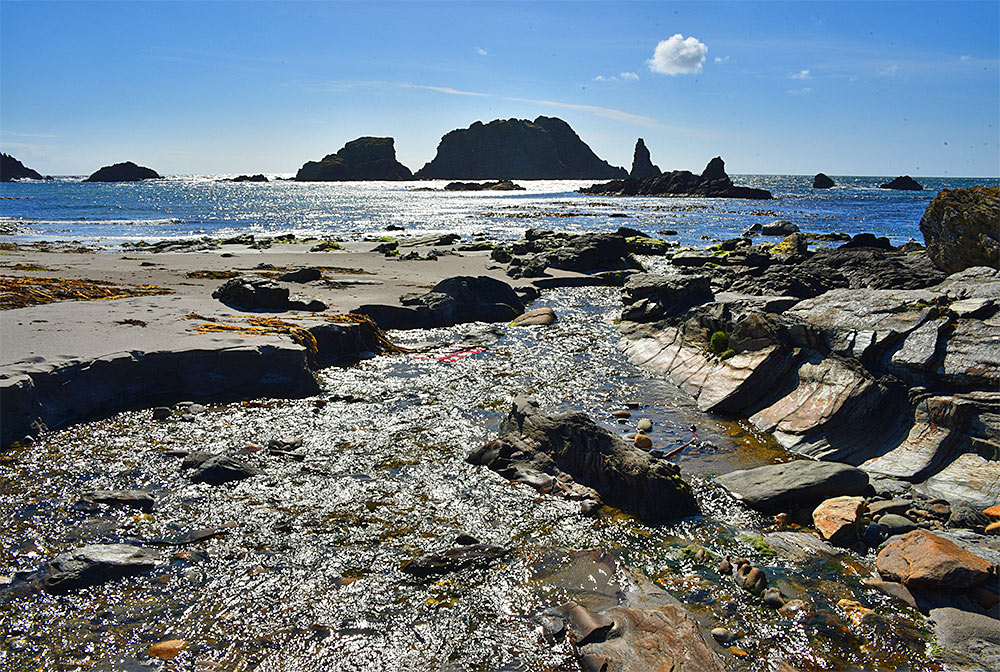 Picture of a burn (stream) flowing over a beach into a bay with rock formations