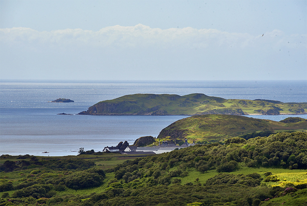 Picture of a coastal distillery seen from a nearby hill