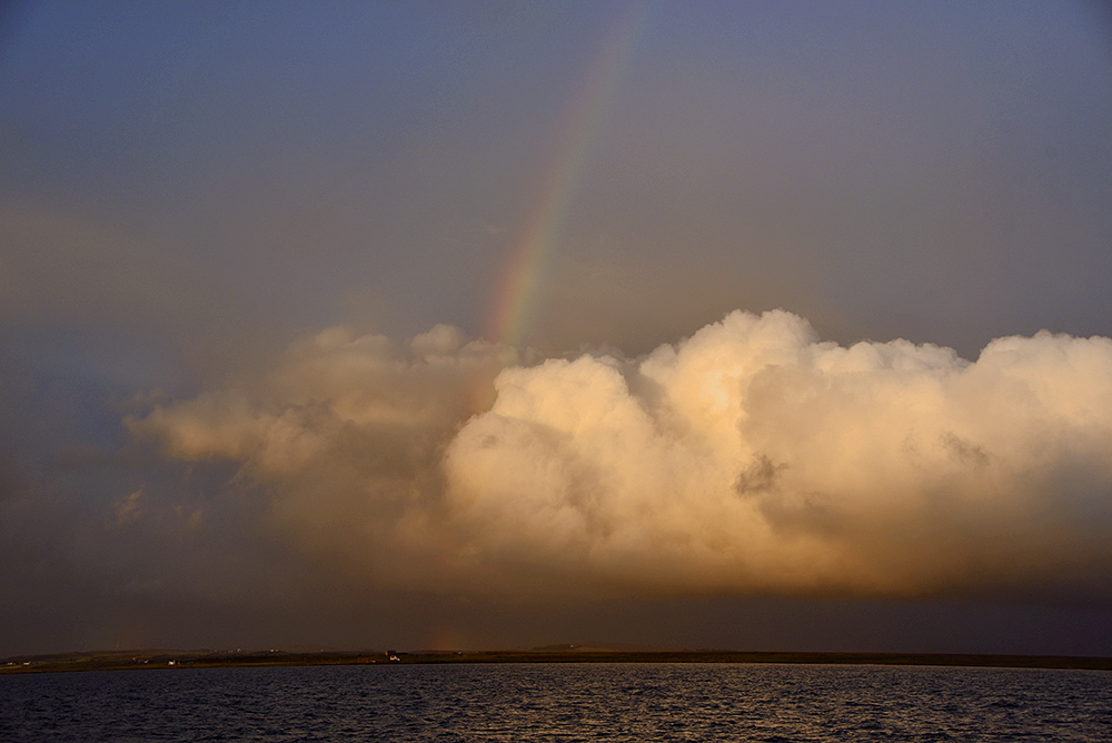 Picture of a cloud over a sea loch in dramatic light, a rainbow above