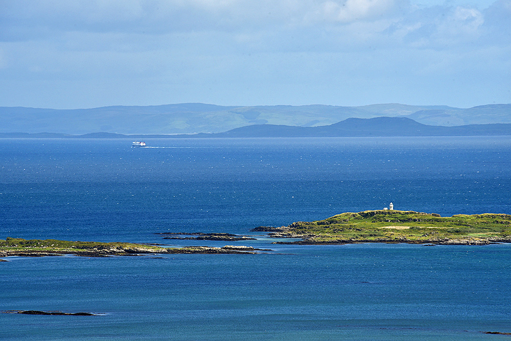 Picture of a view from a coastal hill to a small island with a lighthouse, a ferry in the distance