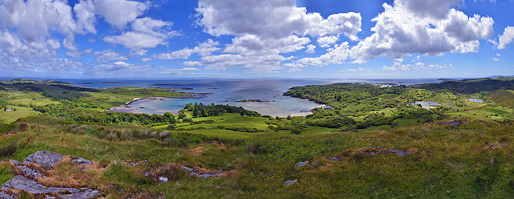 Panoramic picture of a view from a hill over a coastline with bays, islands, skerries