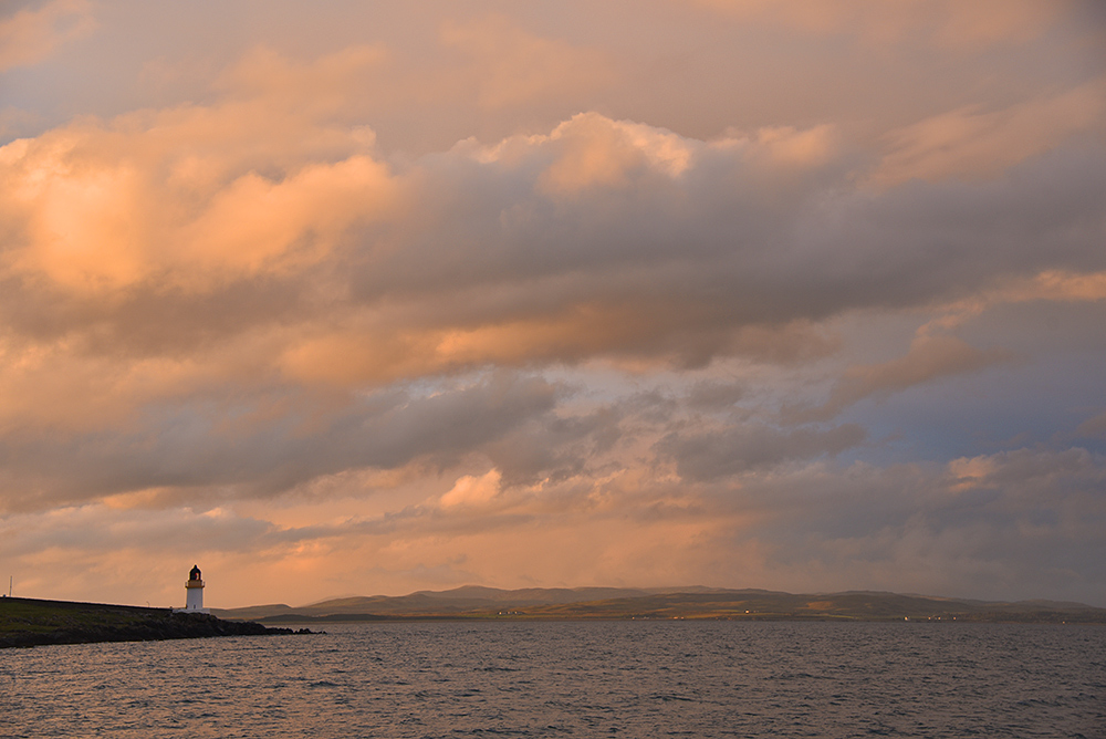 Picture of a cloudy sky in beautiful summer evening light over a sea loch with a small lighthouse on the shore