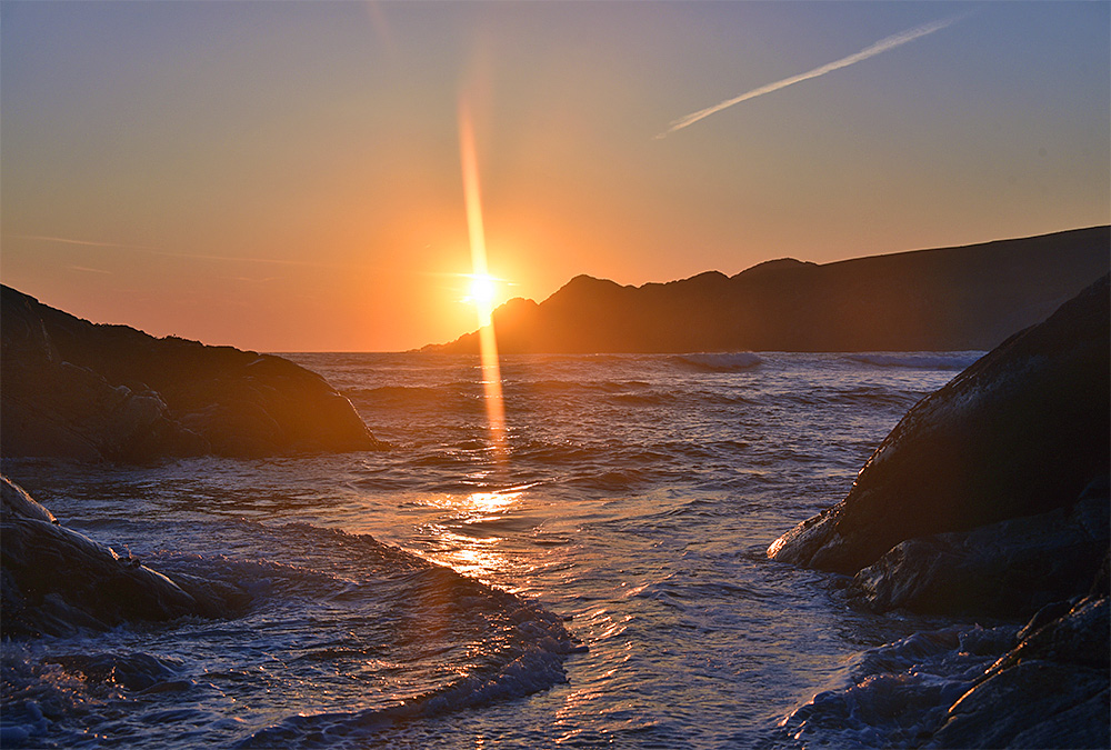 Picture of the sun about to set behind a headland at the end of a bay