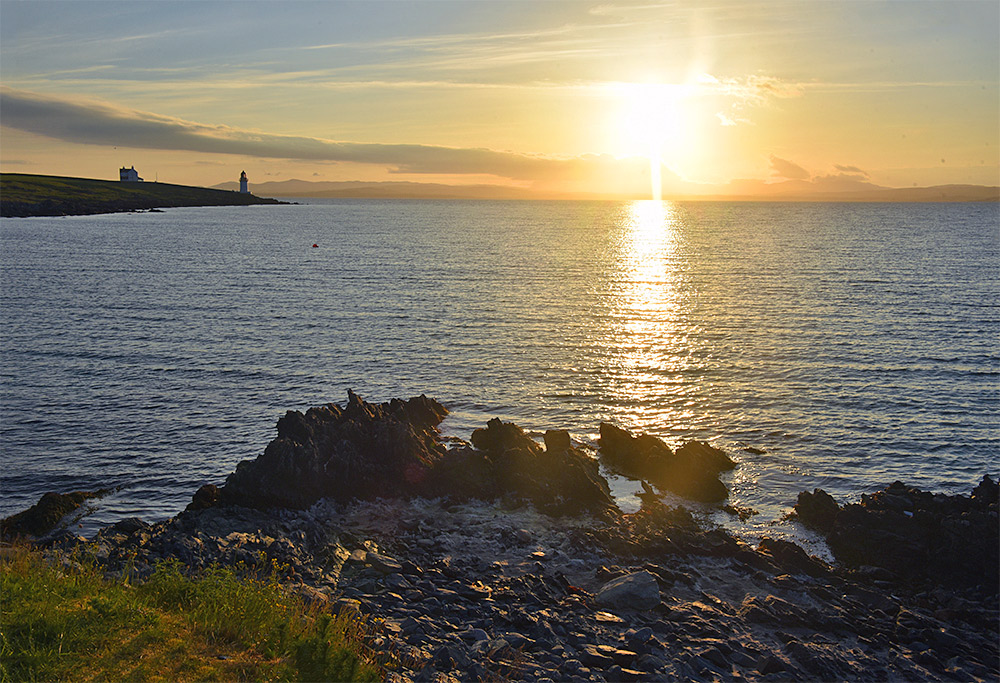 Picture of a view out over a sea loch soon after sunrise, a lighthouse visible in the distance