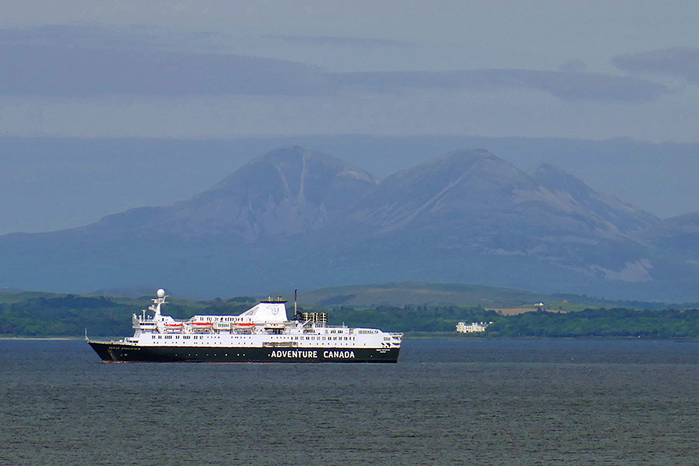 Picture of a cruise liner in a sea loch, three mountains in the background