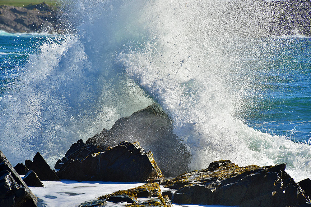 Picture of a wave crashing/smashing over rocks, sending lots of spray into the air