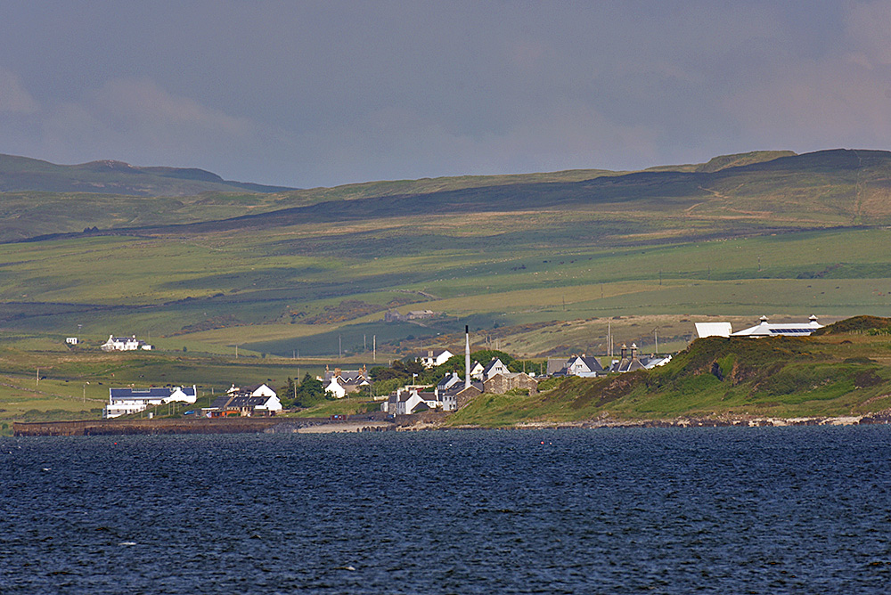 Picture of a coastal village with a pier seen across a sea loch