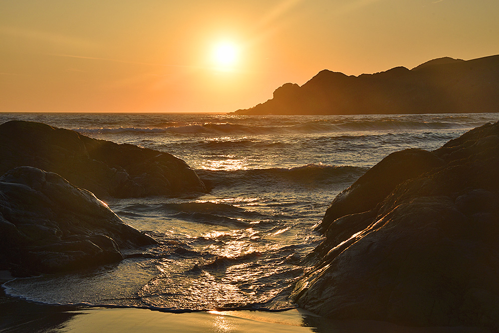 Picture of waves rolling in between rocks on a hazy sunny summer evening