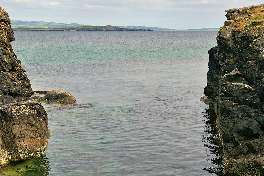 Picture of a view of a coast seen between two rocks