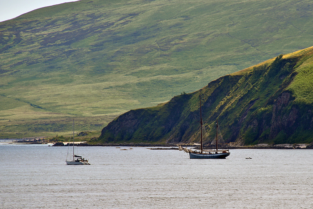 Picture of a modern sailing yacht and an old ketch near a coast