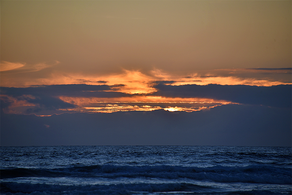Picture of a sunset at the Atlantic behind a bank of clouds