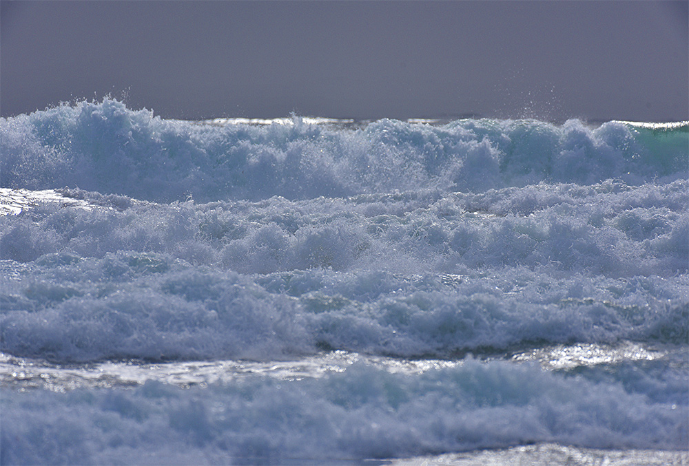 Picture of several breaking waves approaching a beach