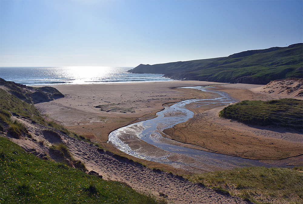 Picture of a view from a dune on to a sandy beach in a bay, a burn/stream flowing at the foot of the dune