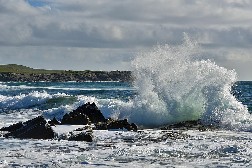 Picture of a wave breaking over jagged rocks, sending water high into the air