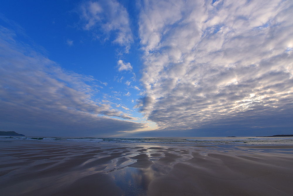 Picture of a big partially cloudy, partially clear sky over a sandy beach
