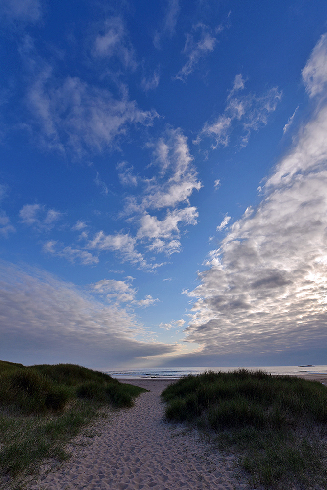 Picture of a partially cloudy, partially clear big sky over a dune path leading to a beach