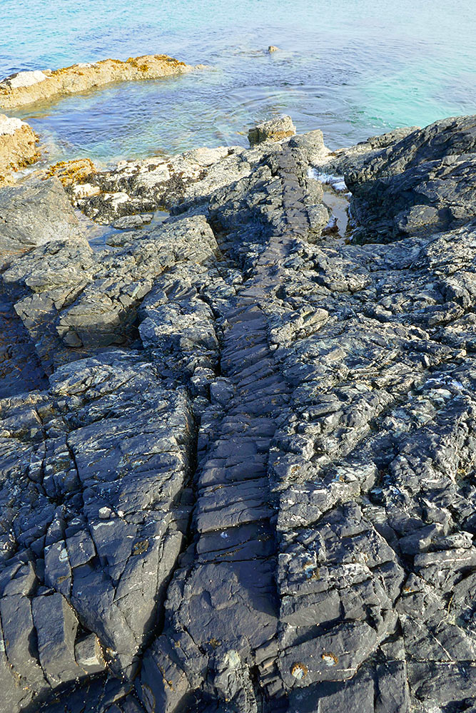Picture of a rock formation looking like tiny steps on a rocky shore leading to water