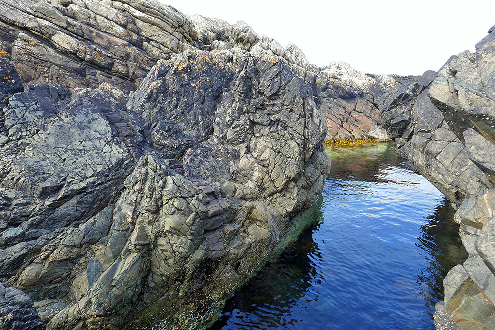 Picture of a cut between rocks on a shore, a rock formation looking like tiny steps on the left side