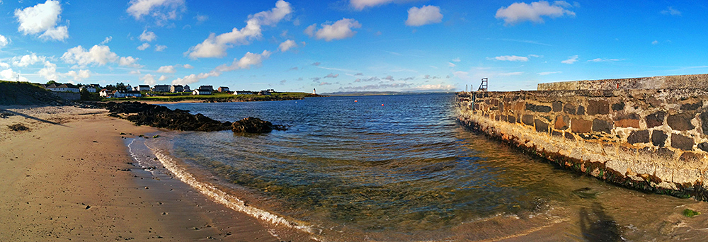 Panoramic picture of a small beach next to a pier, also a lighthouse in the distance