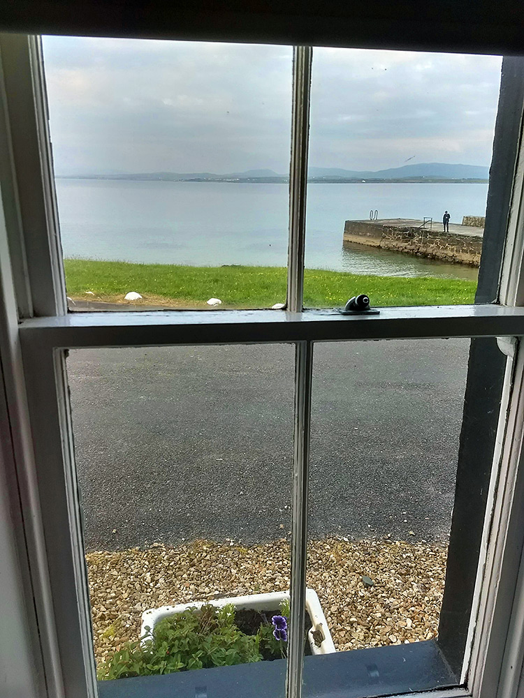 Picture of a view through a cottage window to a pier