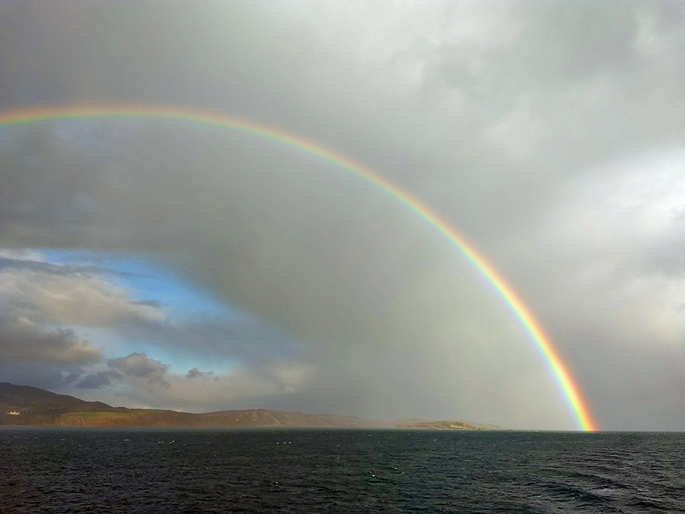 Picture of a rainbow over an island, seen from a passing ferry
