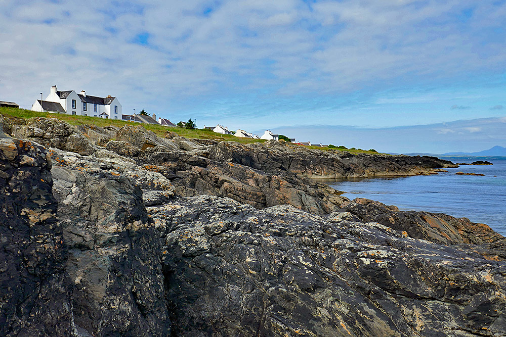 Picture of a rocky shore with a row of house further up