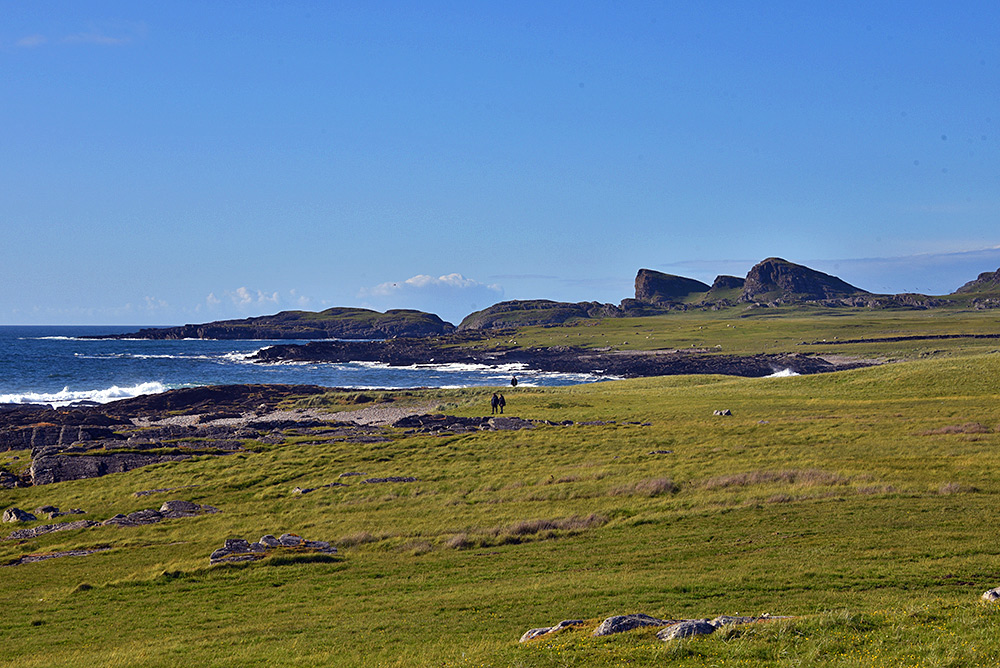 Picture of a coastal landscape with a few walkers approaching