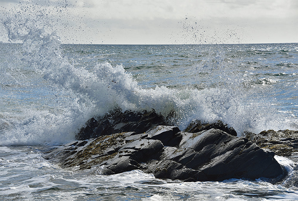 Picture of a wave breaking over rocks, splashing and sending spray into the air