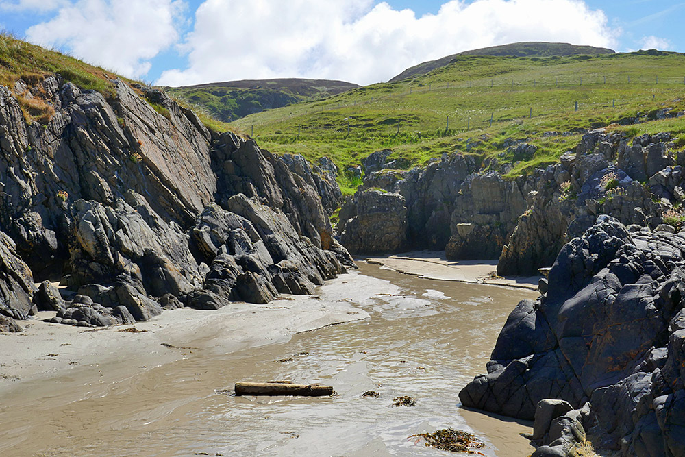Picture of a coastal landscape with hills, rocks and a stream running on to a beach