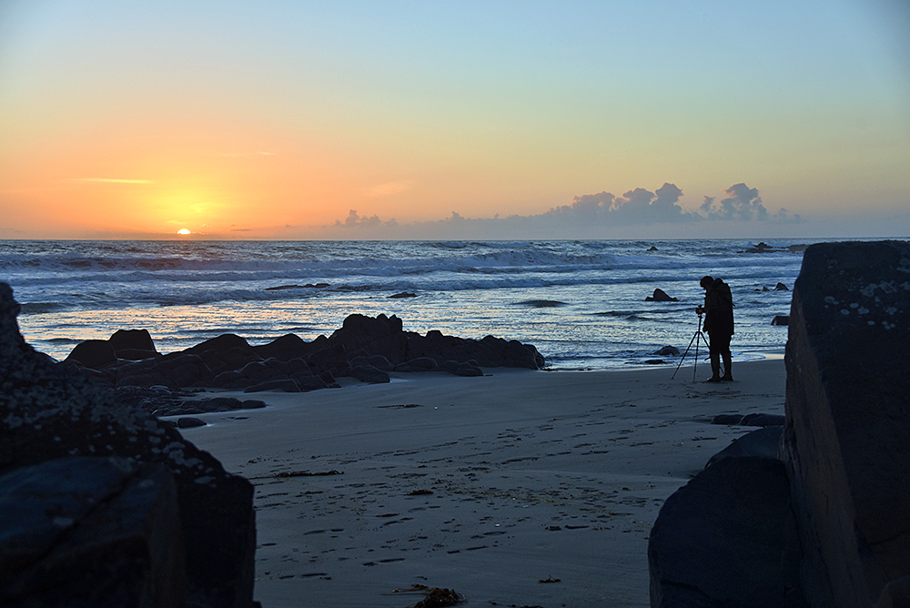Picture of a photographer standing on a beach photographing the sunset