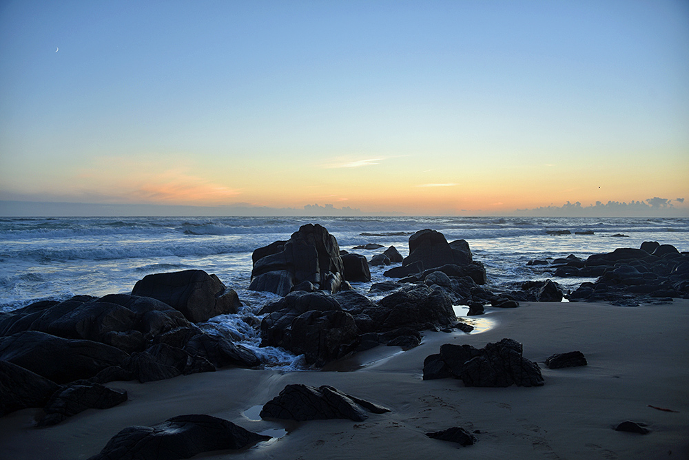 Picture of rocks on a beach in the last light just after sunset, called the gloaming