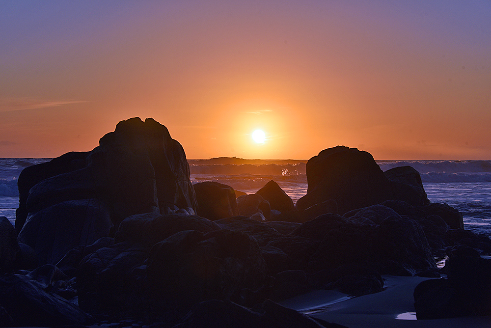 Picture of a colourful sunset behind some coastal rocks and waves rolling in at the coast