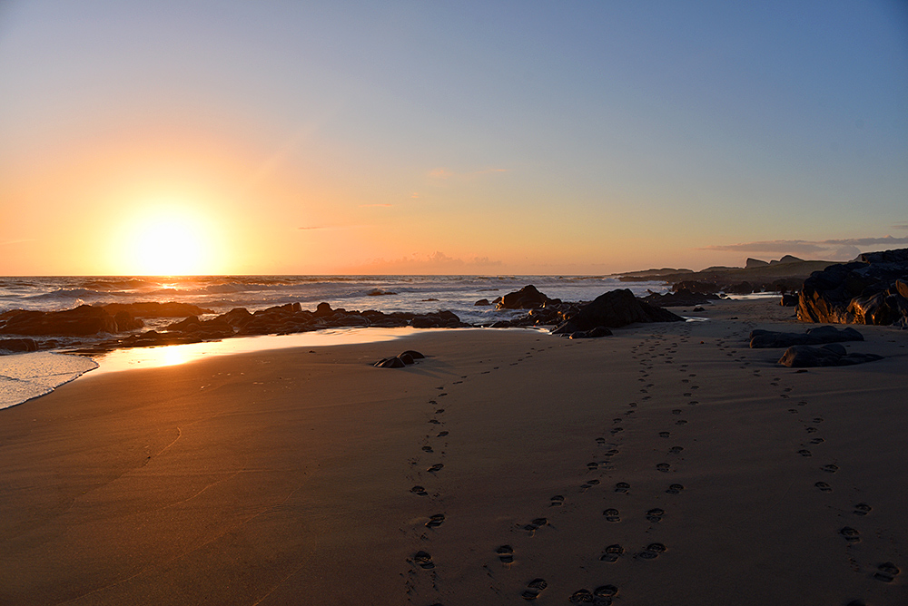 Picture of footsteps on a sandy beach in the late evening light just before sunset