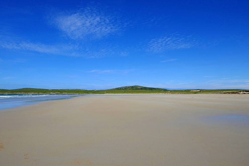 Picture of a wide golden sandy beach under a blue sky