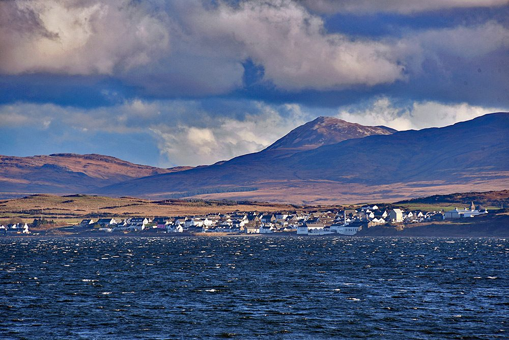 Picture of a coastal village (Bowmore on Islay) seen across a sea loch (Loch Indaal)