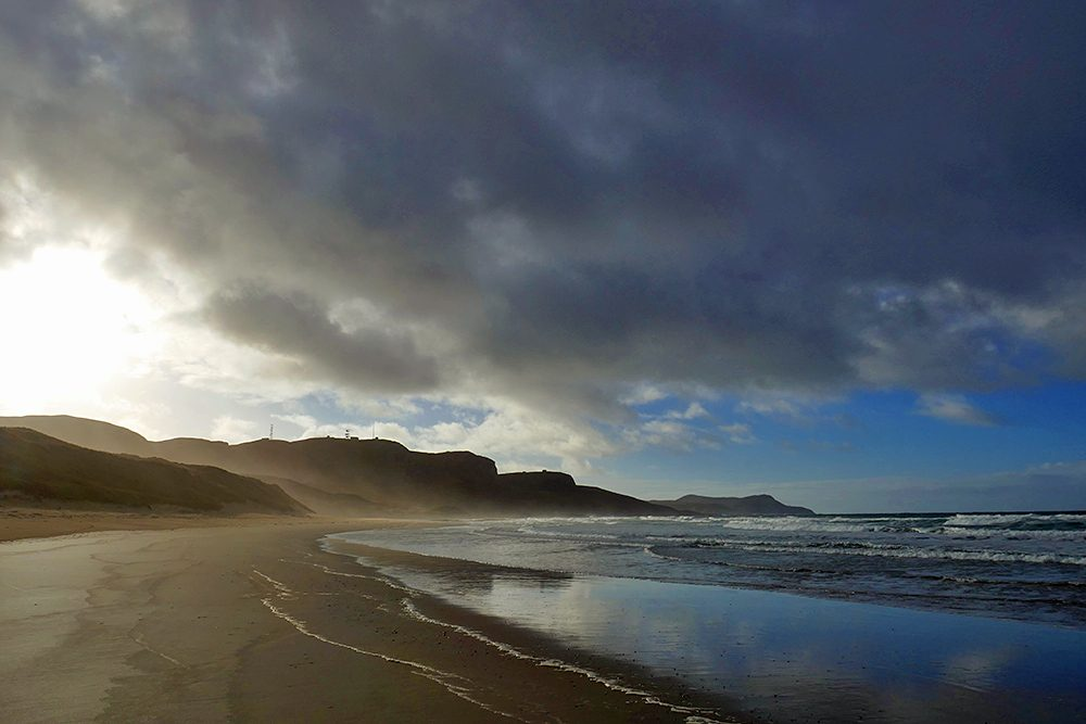 Picture of dark clouds over a bay with a beach, some dramatic mild November light on the beach