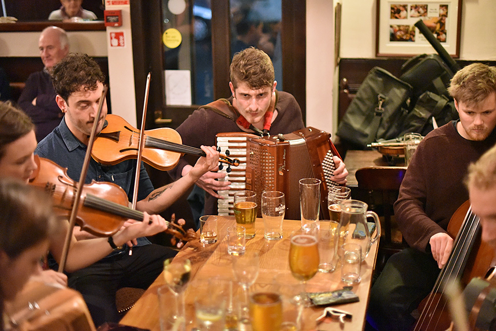 Picture of a group of musicians around a table playing traditional music